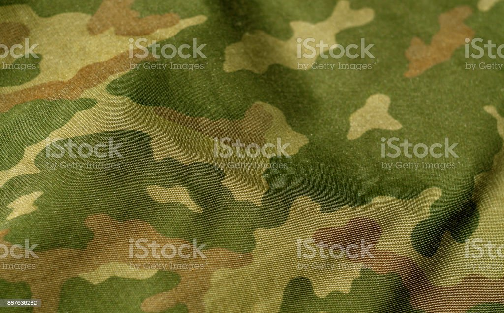 Green and brown color military uniform pattern with blur effect. stock photo