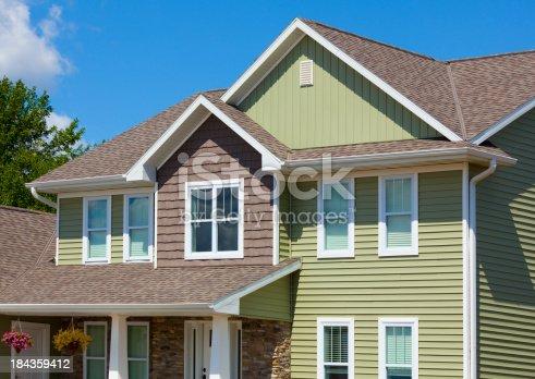Green And Brown House Of Stone Cedar Vinyl Siding Stock