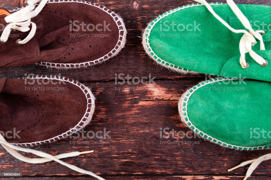 Green and brown suede espadrille shoes on wooden background. stock photo