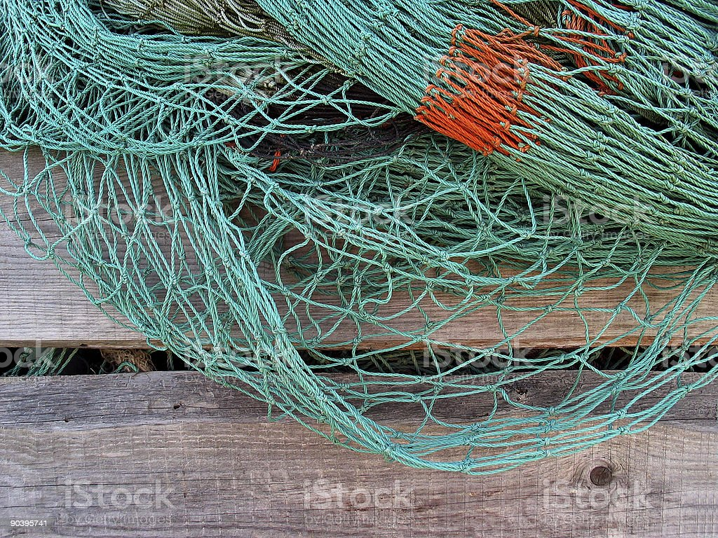 Green and orange fishnet hanging on a wooden fence stock photo