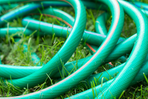 a green and orange hose for watering the garden close up - garden hose stock pictures, royalty-free photos & images