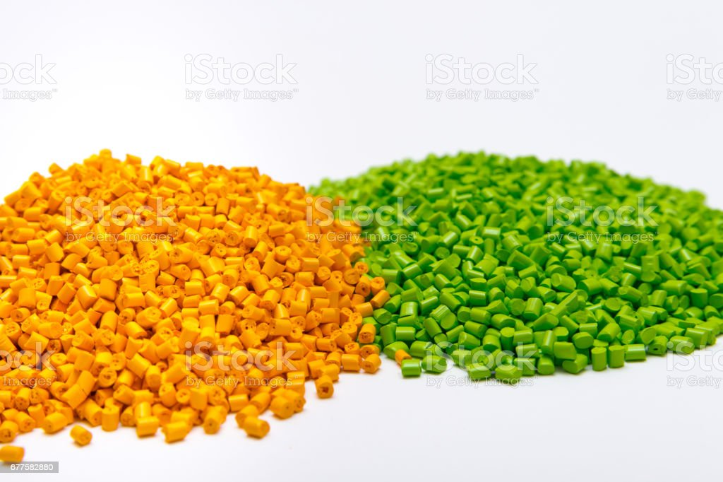 Green and orange plastic pellets on a white background. Polymeric dye for plastics. royalty-free stock photo
