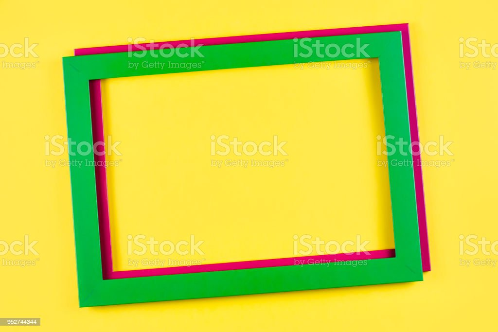 Green and pink color frame on bright yellow background. stock photo