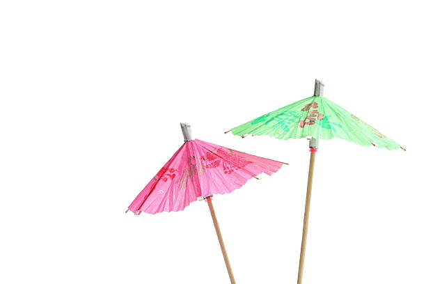 Green and pink open cocktail umbrellas stock photo