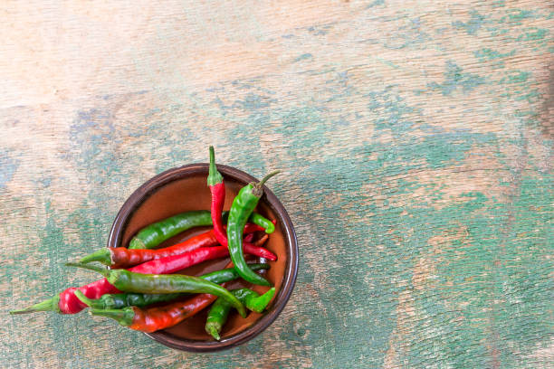 green and red chili on wicker basket on wood table, herbal ingredient in many kinds of spice food on old bluewooden background. top view stock photo