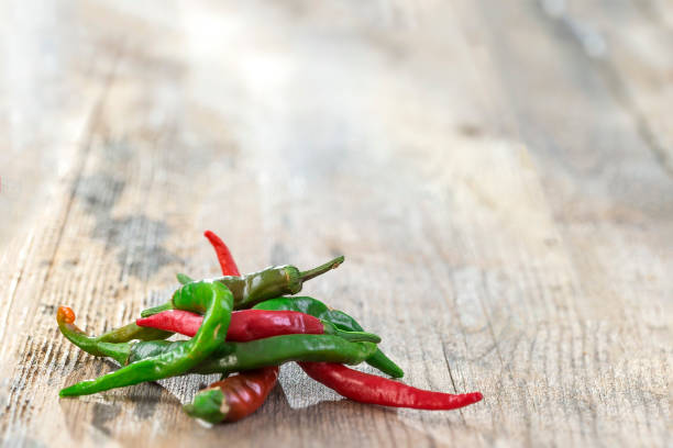 green and red chili , on wood table, important herbal ingredient in many kinds of spice food,Chili peppers on wooden background. stock photo