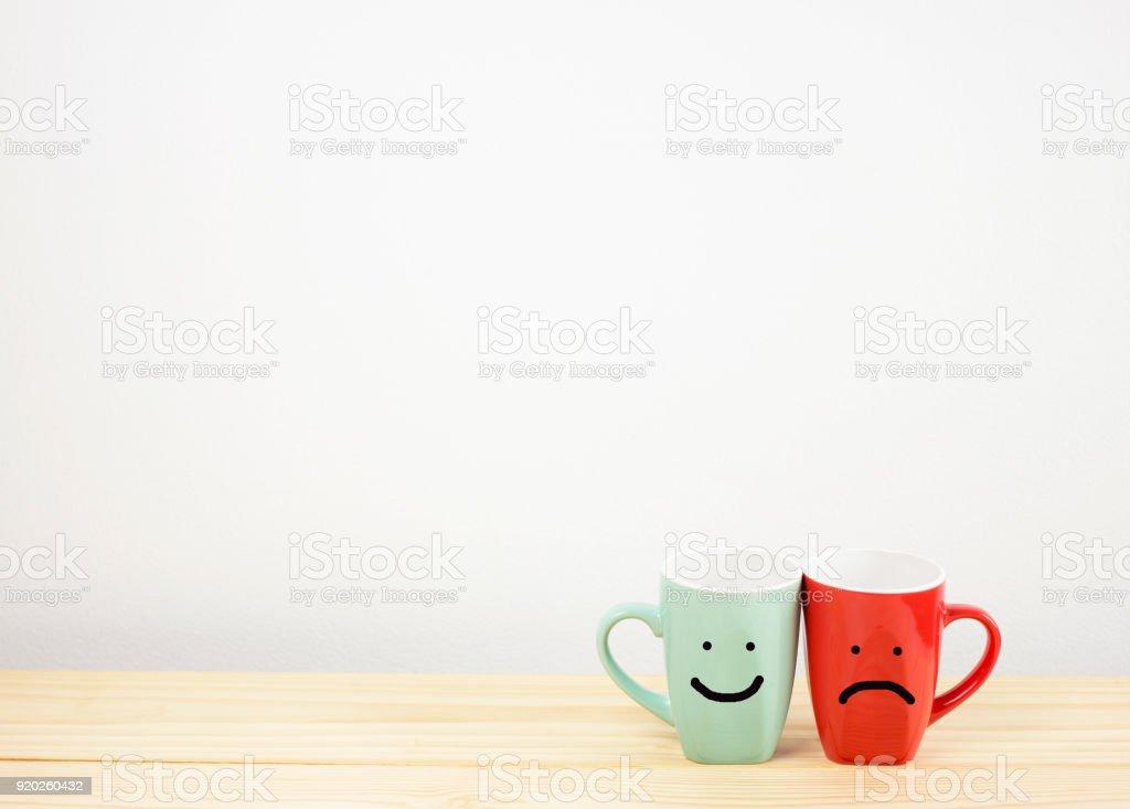 Taza De Café Verde Y Roja Con Sonrisa Y Cara Triste En La Mesa De