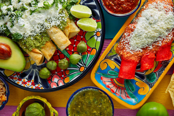 Green and red enchiladas with mexican sauces Green and red enchiladas with mexican sauces mix in colorful table latin american culture stock pictures, royalty-free photos & images