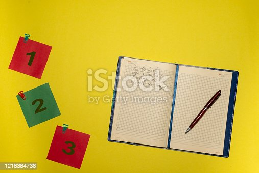 istock green and red stickers and notepad on yellow background 1218384736