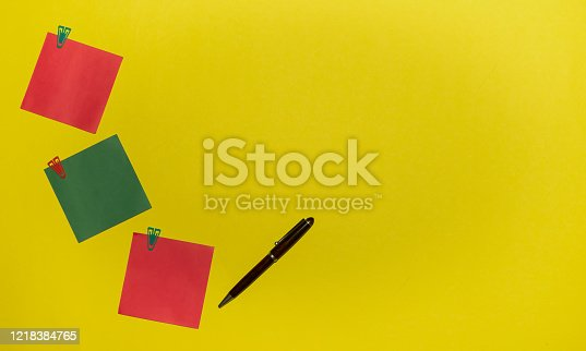 istock green and red stickers with clips and pen on yellow background 1218384765