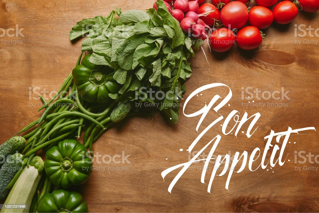 Green and red summer vegetables on wooden table with 'bon appetit' lettering stock photo