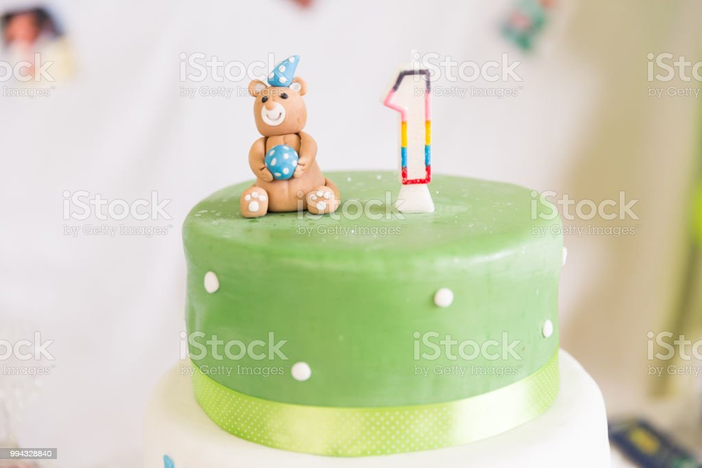 Green And White Birthday Cake With One Year Old Candle Teddy Bear Royalty Free