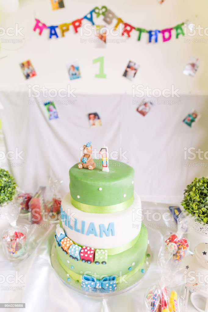 Green And White Birthday Cake With One Year Old Candle Happy Banner In The Background