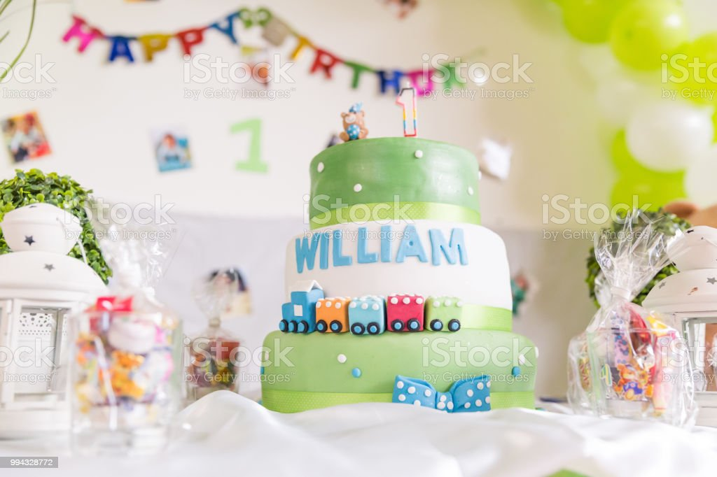 Green And White Birthday Cake With One Year Old Candle Happy Banner In The