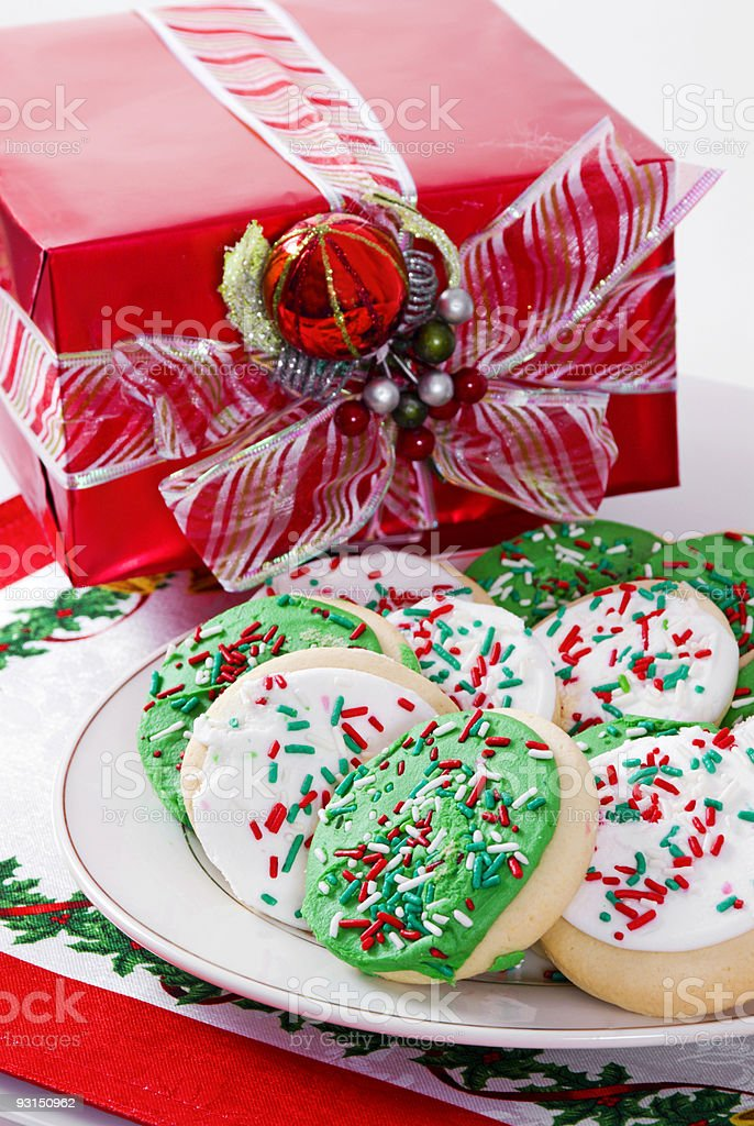 Green and white Christmas cookies and a wrapped Christmas present royalty-free stock photo