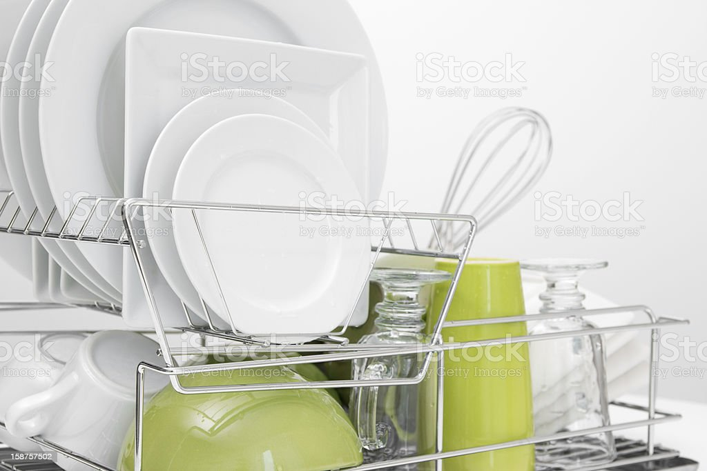 Green and white dishes drying on dish rack stock photo