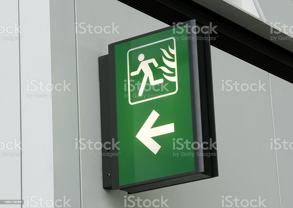 Green and white emergency exit sign on white stock photo