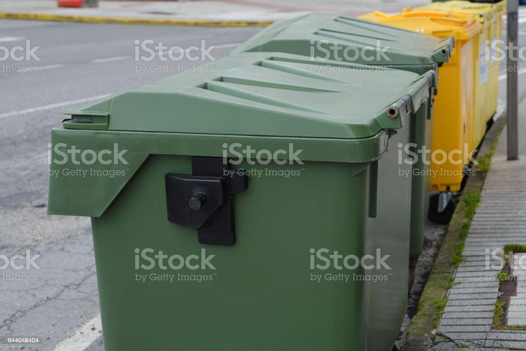 green and yellow garbage cans on the street stock photo