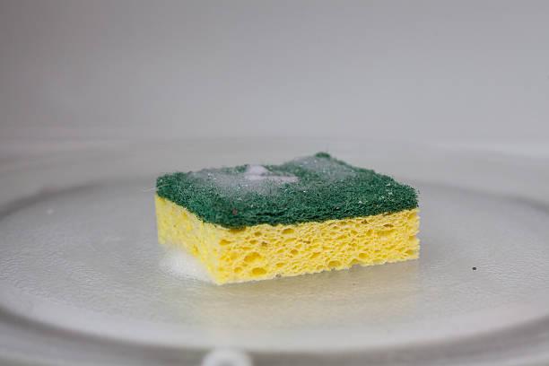 spugna verde e gialla in forno a microonde - spugna per le pulizie foto e immagini stock