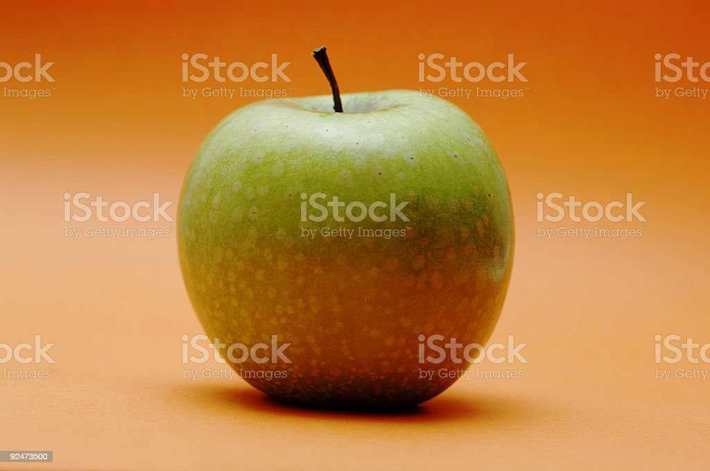 green apple against an orange background royalty-free stock photo