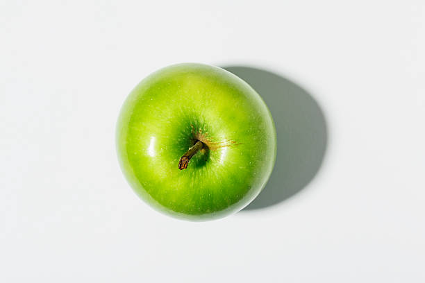 Green Apple against white with strong shadow.
