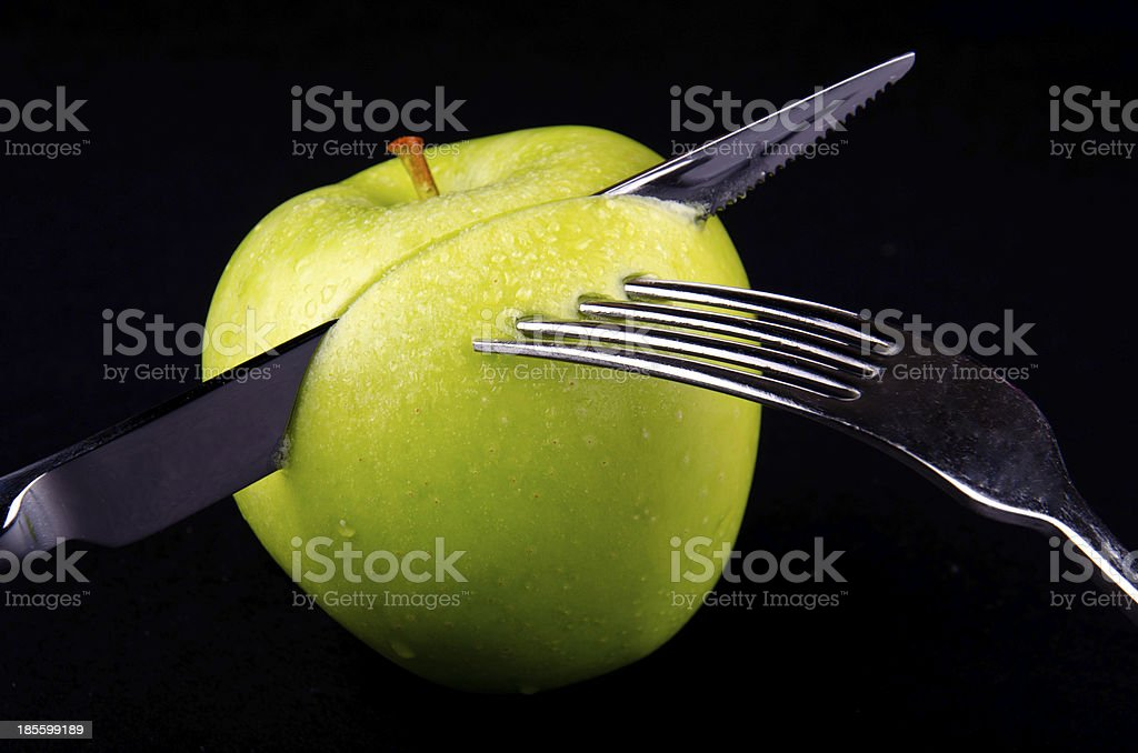 Green apple and a dinner set royalty-free stock photo