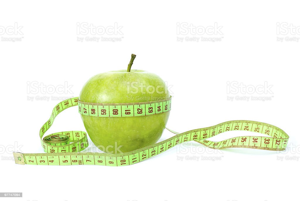 Green apple and measurement tape stock photo