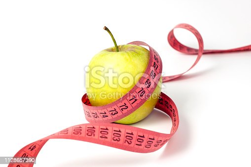 1184112328 istock photo Green apple and measuring tape on white background 1128657390