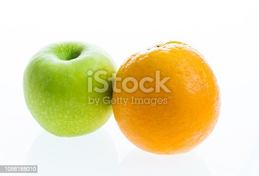 Green apple and orange on white background.