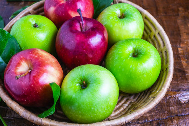 Green apple and red apple in a basket on a wooden background stock photo