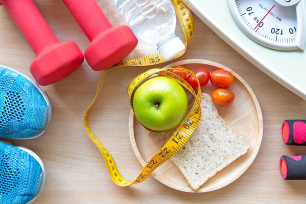Green apple and Weight scale,measure tap with clean water and sport equipment for women diet slimming.  Diet and Healthy Concept stock photo