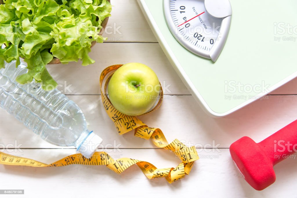 Green apple and Weight scale,measure tap with fresh vegetable, clean water and sport equipment for women diet slimming.  Diet and Healthy Concept - fotografia de stock