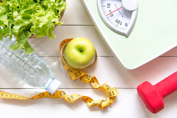 green apple and weight scale,measure tap with fresh vegetable, clean water and sport equipment for women diet slimming.  diet and healthy concept - healthy food imagens e fotografias de stock