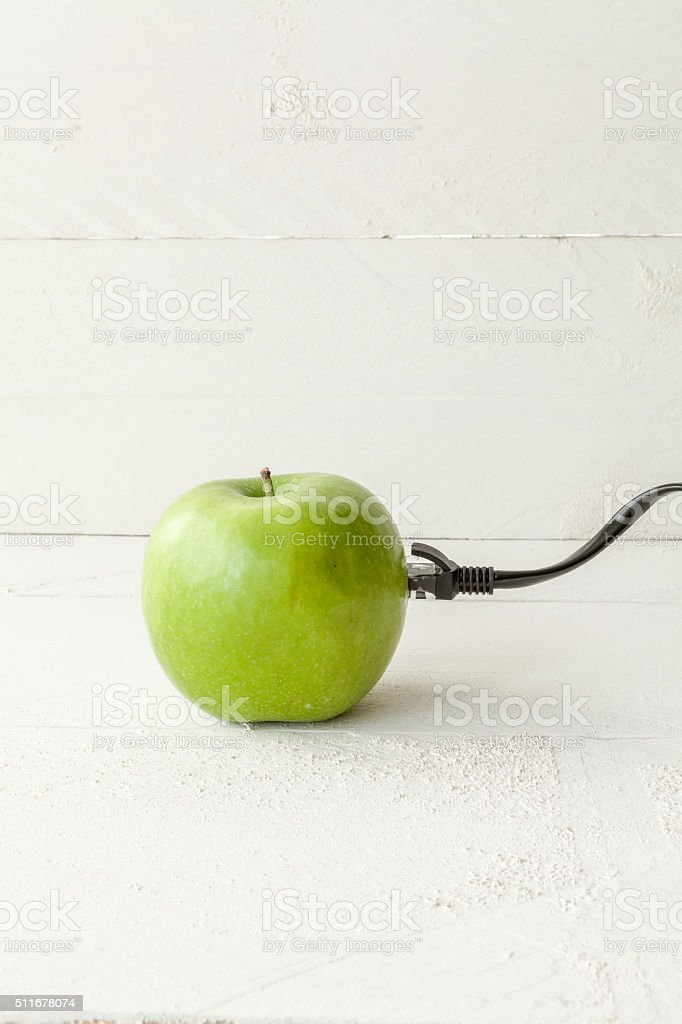 Green apple connected to an ethernet cable stock photo