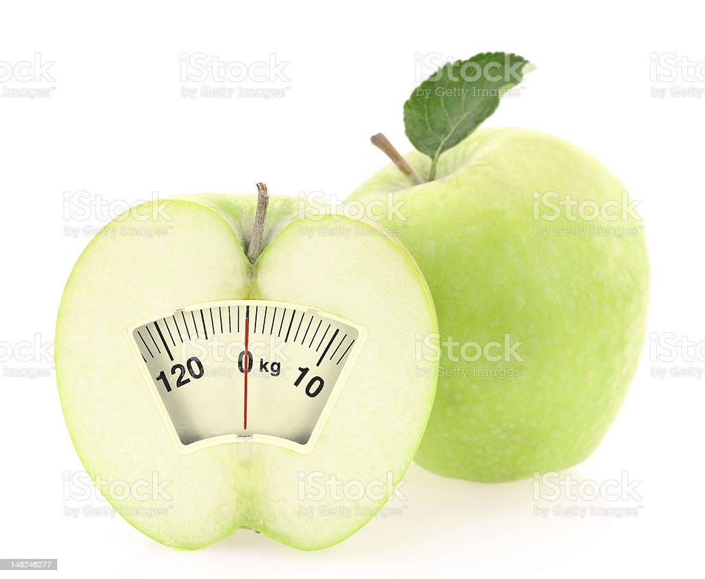 Green apple cut down the center with a scale in the middle stock photo