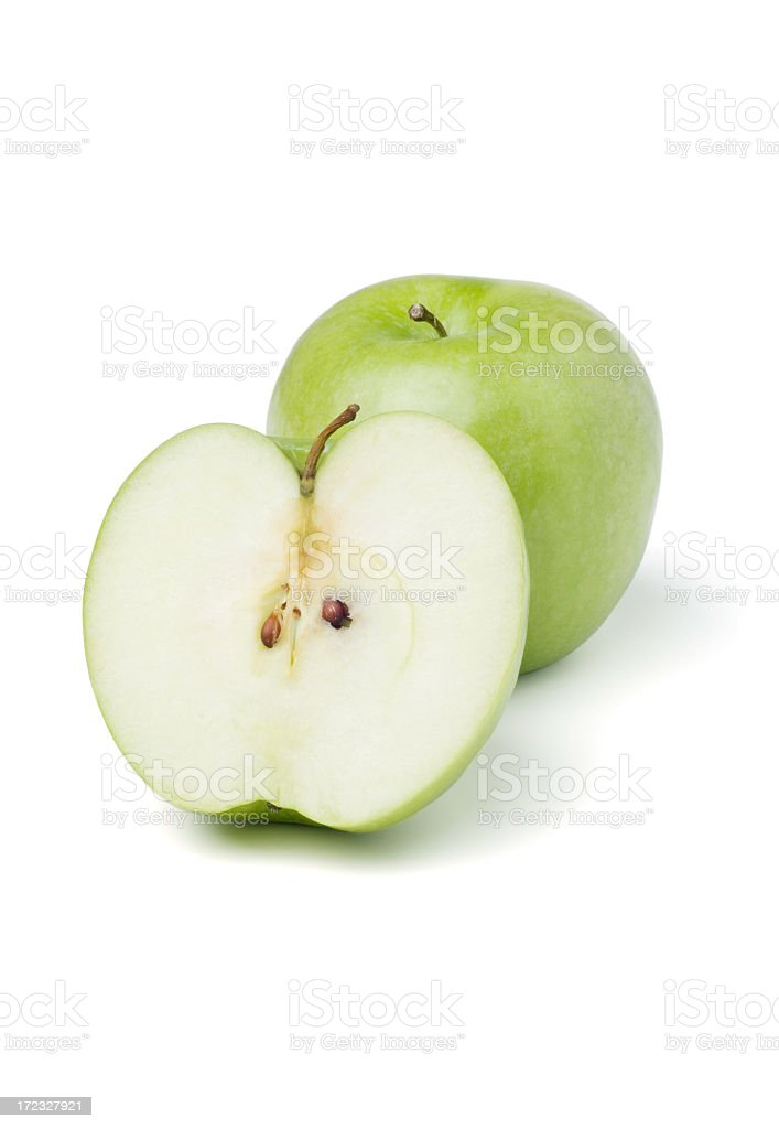 A green apple cut in half on a white background stock photo