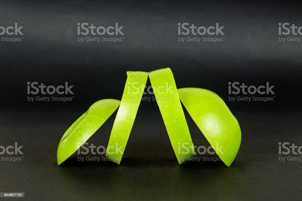 Grüner Apfel geschnitten auf dunklem Hintergrund. – Foto
