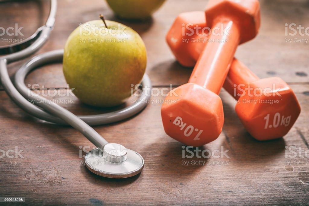 Manzana verde, pesas y un estetoscopio sobre fondo de madera - Foto de stock de Alimento libre de derechos
