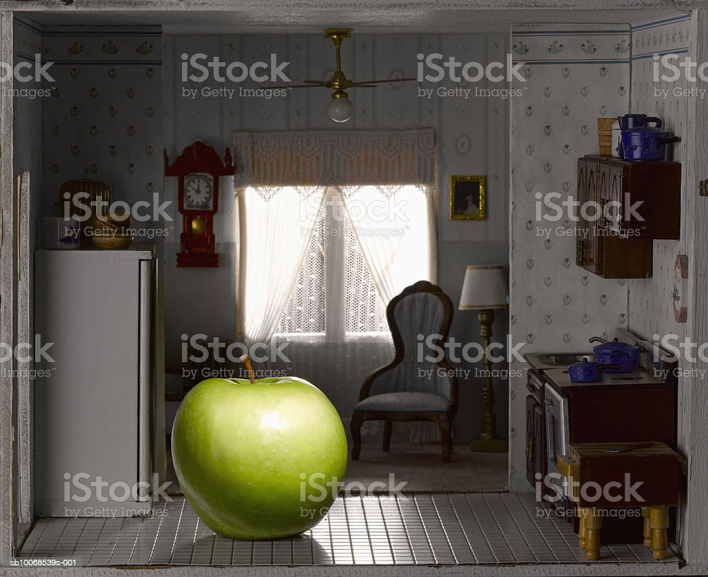 Green apple in domestic kitchen of model house, close-up royalty-free stock photo