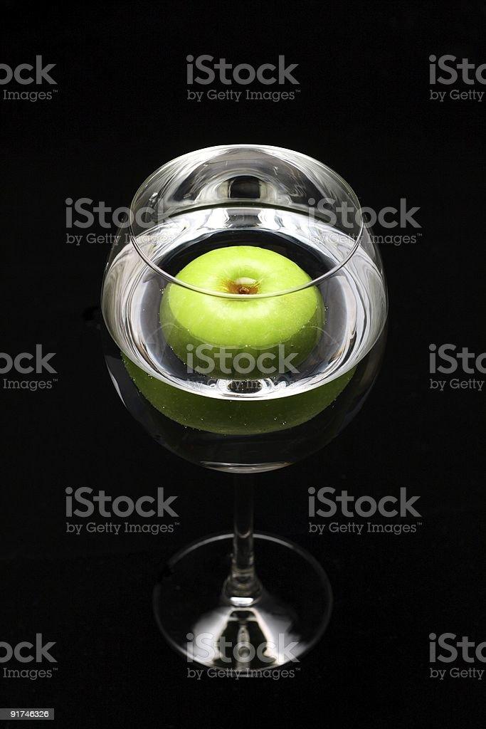 Green apple in wine glass stock photo