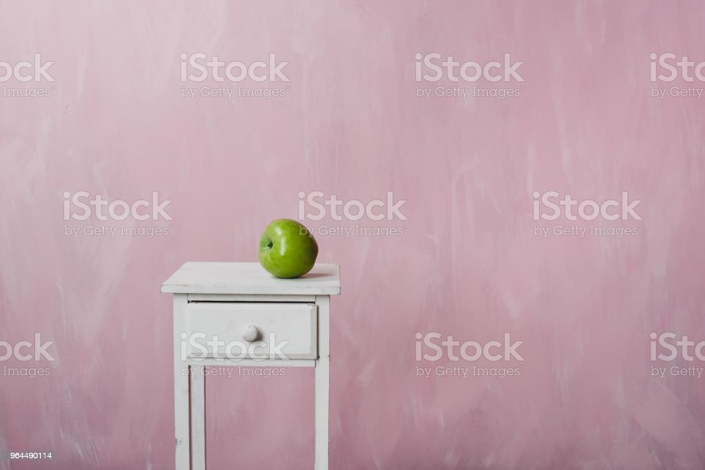 A green apple lies on a white vintage pedestal on a pink background stock photo