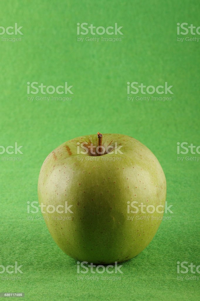 Green apple on green background stock photo