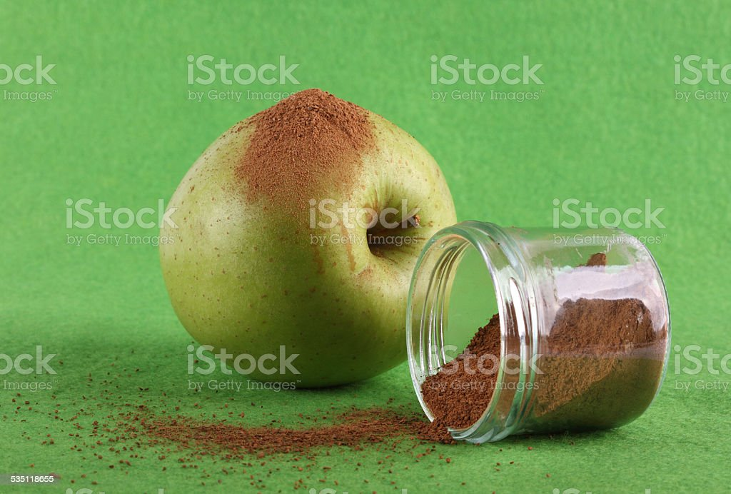 Green apple on green background with cinnamon stock photo