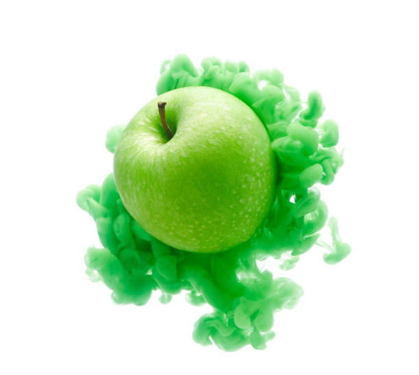 Green apple on ink isolated over white background stock photo