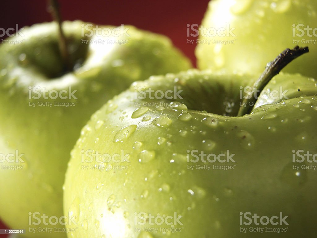 Green apple on red with waterdrops 3 stock photo