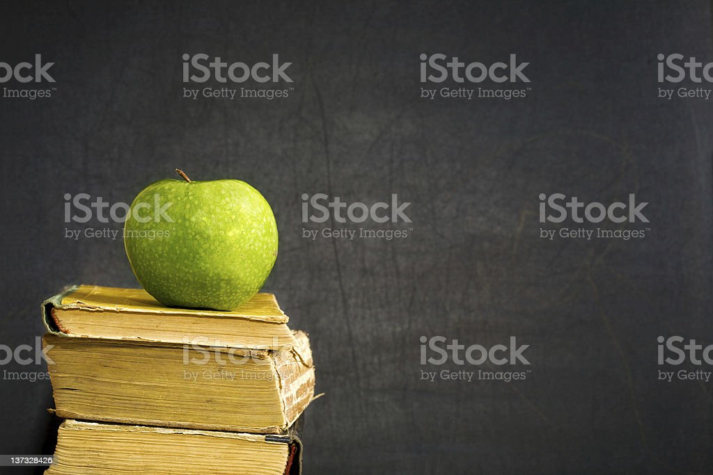 Green apple on textbook royalty-free stock photo