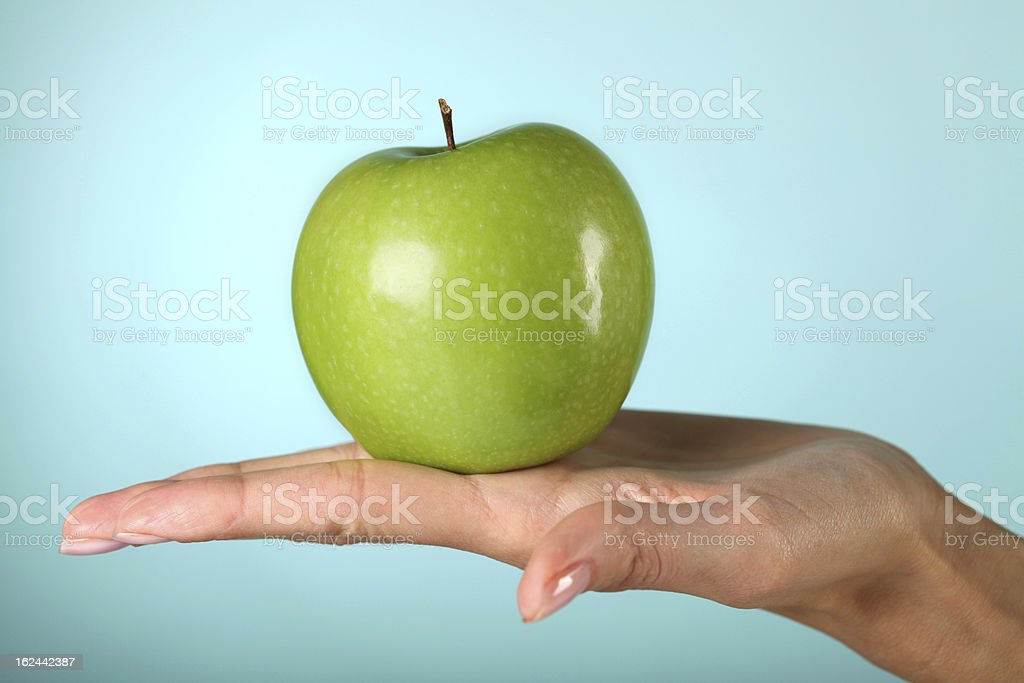 Green apple on the woman's hand stock photo