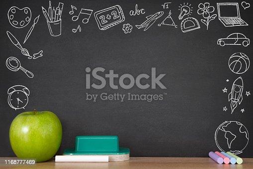 Green apple on wooden school desk with black chalkboard