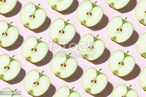 Apple slices in a row on pink background