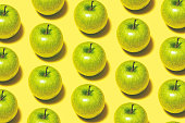 Green apple repetitive flat lay on yellow background